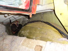 Nothing exits the wheel wells - exception the small owner added or after market drain line.  I inspected the under side of the wheel wells and they have no openings or signs of any openings.  I'm thinking after market - BUT - the yellow paint WAS the original color... so if the rear clip was replaced it was during it's earlier life.