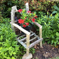 homemade twig chair flower holder with dipladenia plant