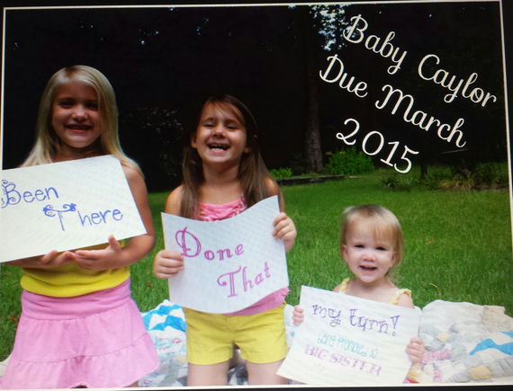 "The signs say ""been there"", ""done that"", ""my turn! Being promoted to big sister march 2015"""