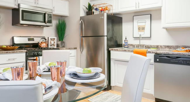 Newly updated kitchens featuring updated cabinetry and counter tops as well as wood-style flooring.